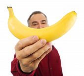 Man Holds Banana In Front Of His Face