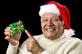 Cheerful Old Man Pointing At Green Wrapped Gift