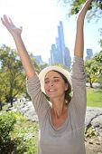 Cheerful girl in central Park lifting arms up