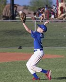 A Youth Baseball Player Catches The Ball