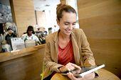 Brunette woman websurfing on tablet in coffee shop