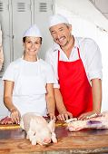 Portrait of confident male and female butchers standing with pork on counter in butchery