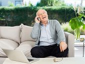 Cheerful senior man laughing while answering smartphone on couch at nursing home porch
