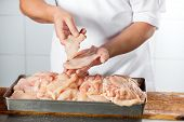 Midsection of mature butcher holding chicken pieces at counter in shop