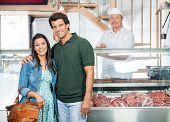 Portrait of happy mature couple standing in butchery