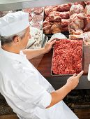 High angle view of butcher holding minced meat at display cabinet in butchery
