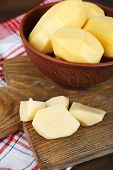Raw peeled potatoes in bowl on cutting board, on wooden background