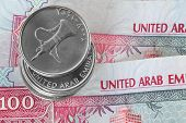 stock photo of dirham  - Closeup of dirham coins on 100 dirhams notes - JPG