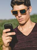 Model Man Portrait With Wooden Sunglasses Outdoors. Man Is Using A Smartphone.