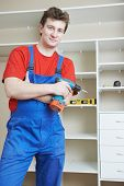 Portrait of happy carpenter worker in front of home built-in cupboard