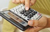 closeup of a young man in casual wear using a calculator