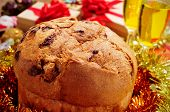 closeup of a panettone, a typical Italian sweet for Christmas time, on a table with champagne and gifts