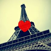 a picture of the Eiffel Tower in Paris, France, with a retro effect, with a heart icon like the like buttons used in social networks to depict the idea of liking the picture