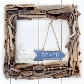 foto of driftwood  - Driftwood frame and beach sign with cockle shells over wooden white background - JPG