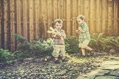 picture of easter eggs bunny  - A boy collects Easter eggs during an egg hunt while his younger brother holds a yellow bunny - JPG