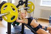 foto of barbell  - Sports young woman doing exercises with barbell on bench in the gym - JPG