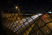 pic of chain link fence  - Long exposure of highway at night as seen from the walkway above through a chain link fence - JPG