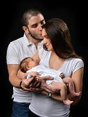 image of infant  - Beautiful mother and father smiling holding their newborn infant child baby boy on a black background - JPG