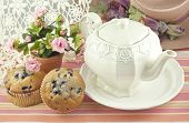 stock photo of tea party  - A ladies tea party with a vintage teapot fresh baked blueberry muffins and pretty decorations perfect for mothers day - JPG
