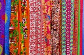 pic of stall  - Rows of colourful silk scarfs hanging at a market stall in Thailand - JPG