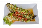 stock photo of snakehead  - Deep fried snakehead fish serve with herb and spicy sauce isolated on white with clipping path  - JPG