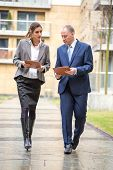 image of real-estate-team  - Two business people walking and discussing outside the office
