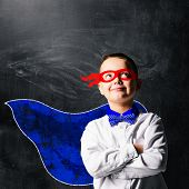 stock photo of blindfolded man  - school boy wearing a superhero costume with blackboard behind him - JPG