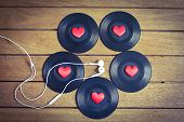 stock photo of jukebox  - Vinyl records with red love hearts and earphones on a wooden table top - JPG