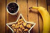 picture of dry fruit  - A bowl of healthy granola with a banana and dried fruit - JPG