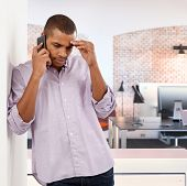 stock photo of afro  - Troubled casual afro american man with mobile phone at home - JPG