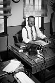 picture of 1950s style  - Confident businessman working at office desk and smiling at camera 1950s style - JPG