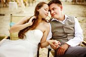 pic of couple sitting beach  - Romantic young couple sitting on the beach resting after wedding ceremony - JPG