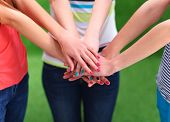 image of joining hands  - People joining their hands  on green grass  - JPG