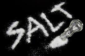image of salt shaker  - A salt shaker tipped over spilling salt on a reflective black surface with a black studio background - JPG