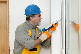 pic of cartridge  - Construction worker caulking door or window with silicone glue using cartridge - JPG
