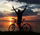 picture of dirt-bike  - silhouette of a man with a mountain bike on the river bank at sunset - JPG