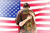stock photo of reunited  - Solider reunited with mother against rippled us flag - JPG