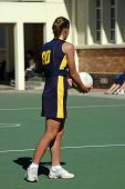 stock photo of netball  - An active caucasian young sportswoman holding a ball in her white hands playing netball sports on the field outdoors - JPG