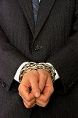 businessman with hands tied by chains