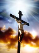 christ in cross against a dramatic sky with divine light