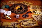esoteric atmosphere with astrological symbols, runes, healing stones, pendulum and magic pentragram