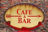 A rusty old retro arrow sign with the text Cafe and Bar