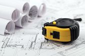 rolls of architectural house plans & tape measure
