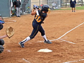 foto of fastpitch  - Fastpitch softball girl after having made contact finishing the swing - JPG
