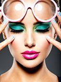 Beautiful Face of a woman with green vivid make-up of eyes and pink glasses. poster
