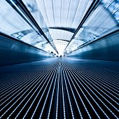 Moving blue travolator in airport hall, square composition