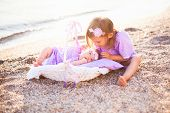 Little Sisters Are On Sea Beach. Two Girls Are In Lilac And Lavender Dresses. Baby Lies In Wicker Ba poster