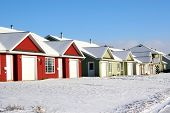A row of new homes covered with newly fallen snow.