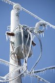 Ice encrusted power lines and transformer on a brilliant winter day.