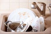 Pile of dirty dishes like plates, pot and cutlery in the light beige granite sink